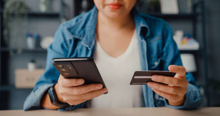 Young asia lady use cellphone order online shopping product and paying bills with credit card in living room interior. Stay at house, Self quarantine activity, Fun activity for coronavirus prevention.