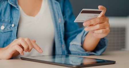 Young asia lady using tablet order online shopping product and paying bills with credit card in living room interior. Stay at house, Self quarantine activity, Fun activity for coronavirus prevention. Foto de archivo