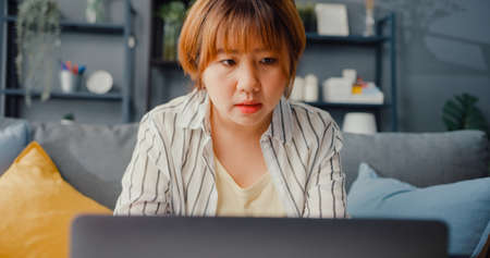 Freelance Asia lady casual wear using laptop online learning in living room at house. Working from home, remotely work, distance education, social distancing, quarantine for corona virus prevention.