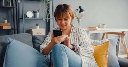 Young Asia lady using smartphone text message or check social media on sofa in living room at house. Work from home, play game, shopping online, social distance, quarantine for coronavirus prevention. Foto de archivo