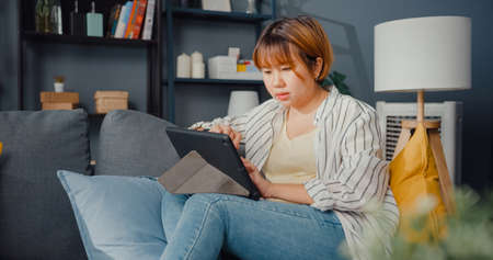 Freelance Asia lady casual wear using tablet online learning in living room at house. Working from home, remotely work, distance education, social distancing, quarantine for corona virus prevention.