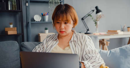 Freelance Asia lady feel headache while sitting on couch with laptop online learn in living room at house. Working from home, remotely work, social distancing, quarantine for corona virus prevention.