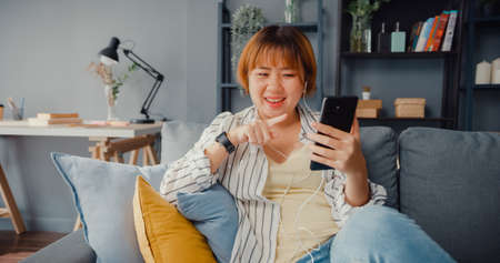 Young Asia lady using smart phone video call talk with family on sofa in living room at house. Work from home remotely during covid-19 lockdown, social distance, quarantine for coronavirus prevention.