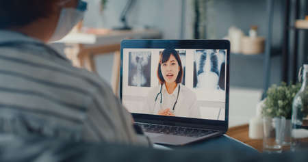 Young Asia girl wear protective face mask using laptop talk about disease in video call with senior doctor online consultation in living room at house. Social distancing, quarantine for coronavirus. Foto de archivo