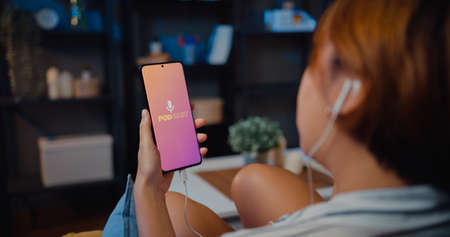 Young attractive Asia lady wear headphones using phone listen digital music podcast online channel sit on sofa in living room at house night. Social distancing, quarantine for coronavirus prevention. Foto de archivo