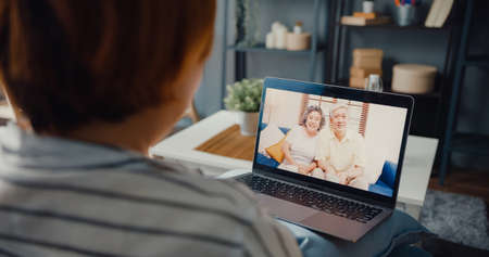 Young Asia girl using laptop video call meeting talk with elderly family dad and mom while work from home sitting on sofa at living room. Social distancing, quarantine for corona virus prevention.
