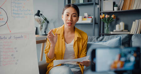 Young Asia lady english teacher video conference calling on smartphone talk by webcam learn teach in online chat at home. Remote classroom, Social distancing, quarantine for corona virus prevention.