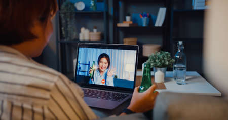 Youth Asia teen girl drink beer having fun happy moment night party event online celebration via video call in living room at house at night. Social distancing, quarantine for coronavirus prevention.