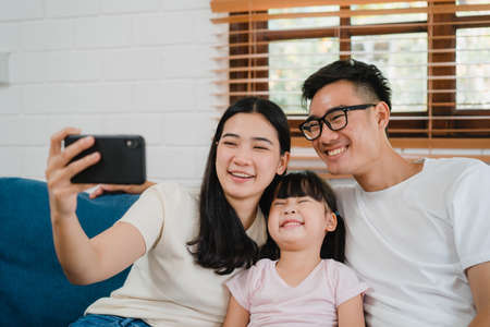 Happy cheerful Asian family dad, mom and kids having fun and using smart phone video call on sofa at house. Self-isolation, stay at home, social distancing, quarantine for  virus prevention. Imagens