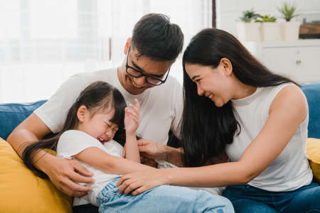 Happy cheerful Asian family dad, mom and daughter having fun cuddling playing on sofa while birthday at house. Self-isolation, stay at home, social distancing, quarantine for  virus prevention.