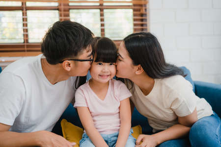 Happy Asian family dad, mom and daughter embracing kissing on cheek congratulating with birthday at house. Self-isolation, stay at home, social distancing, quarantine for  virus prevention. Imagens