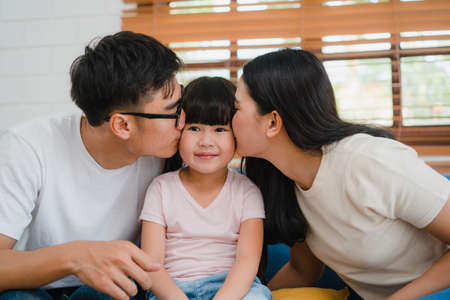 Happy Asian family dad, mom and daughter embracing kissing on cheek congratulating with birthday at house. Self-isolation, stay at home, social distancing, quarantine for virus prevention.