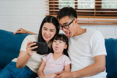 Happy cheerful Asian family dad, mom and kids having fun and using smart phone video call on sofa at house. Self-isolation, stay at home, social distancing, quarantine for virus prevention.