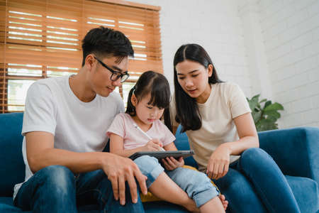 Happy Asian family dad, mom and daughter using computer tablet technology sitting sofa in living room at house. Self-isolation, stay at home, social distancing, quarantine for virus prevention.