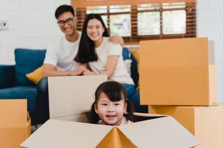 Happy Asian young family homeowners bought new house. Korean Mom, Dad, and daughter playing together during unpacking in new home after moving in relocation sitting on floor with boxes together.