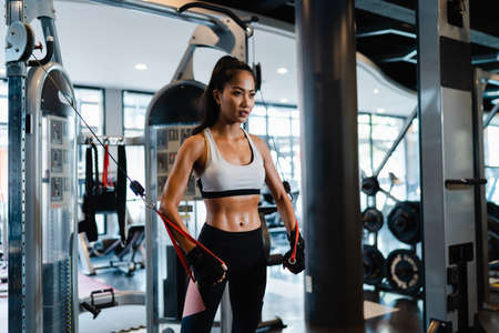 Young Asia lady exercise doing exercise-machine Cable Crossover fat burning workout in fitness class. Athlete with six pack, Sportswoman recreational activity, functional training, healthy lifestyle. Foto de archivo
