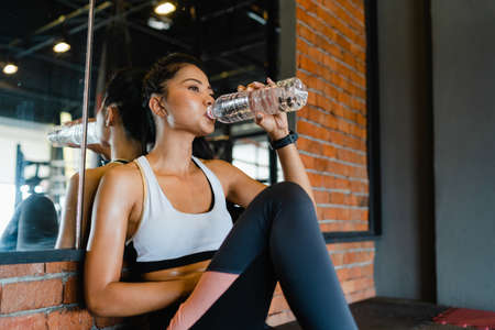 Beautiful young Asia lady exercise drinking water after fat burning workout in fitness class. Athlete with six pack, Sportswoman recreational activity, functional training, healthy lifestyle concept.