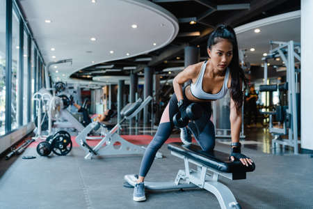 Beautiful young Asia lady exercise doing lifting barbell fat burning workout in fitness class. Athlete with six pack, Sportswoman recreational activity, functional training, healthy lifestyle concept. Foto de archivo
