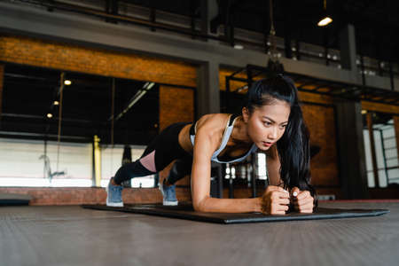 Happy young Asia lady exercise doing plank fat burning workout in fitness class. Athlete with six pack, Sportswoman recreational activity, functional training, healthy lifestyle concept. Foto de archivo