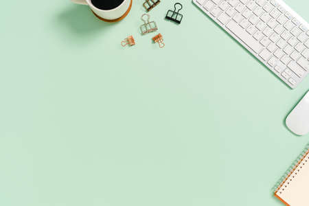 Minimal work space - Creative flat lay photo of workspace desk. Top view office desk with keyboard and mouse on pastel green color background. Top view with copy space, flat lay photography.