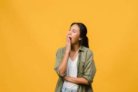 Portrait of Young Asia lady with negative expression, bored yawning tired covering mouth with hand in casual clothing isolated on yellow background with blank copy space. Facial expression concept