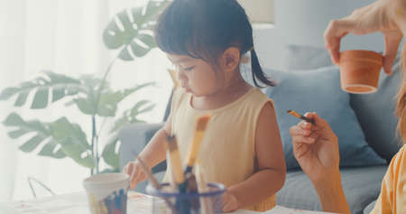 Happy cheerful Asia family mom teach girl paint use album and colourful pencils having fun relax on couch in living room at house. Spending time together, Social distance, Quarantine for coronavirus.