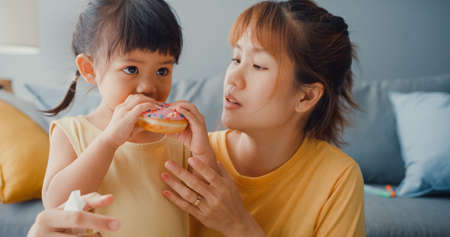 Happy cheerful Asia family mom teach toddler girl paint ceramic pot having fun relax on table in living room at house. Spending time together, Social distance, Quarantine for coronavirus prevention.