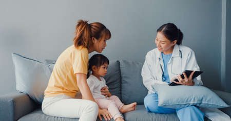 Young Asia female pediatrician hold stethoscope exam little girl patient visit doctor with mother sit on couch in living room at house. Medical care insurance, Visit patient at home concept.