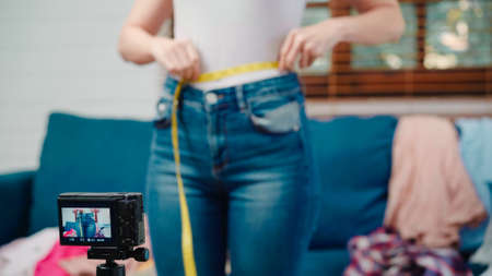 Asian stylist fashion influencer designer women using camera streaming and live to sell clothes, product, and accessories business, e-commerce broadcast online on sofa in living room at home. Imagens