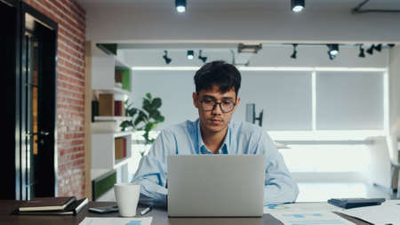 Asian creative man drawing work plan on paper board. Young professional business male think and write information reminder on paper on brick, business situation, startup in Loft office concept. Imagens