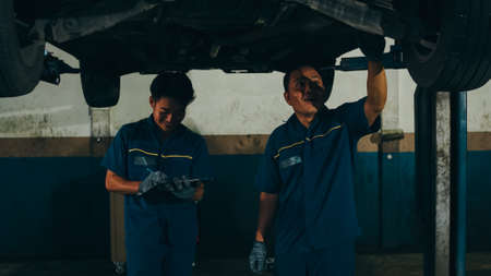 Two professional car mechanic using paperwork makes the oil and engine check to the car on lifted automobile at repair service station at night. Skillful Asian guy in uniform fixing car. Car service. Imagens