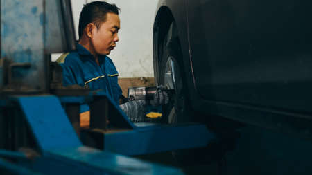 Professional car mechanic screwing details of car engine on lifted automobile at repair service station. Skillful Asian guy in uniform fixing car at mechanics garage at night. Imagens
