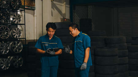 Two professional car mechanic screwing details of car engine on lifted automobile at repair service station. Skillful Asian guy in uniform fixing car at garage night. Car service concept.