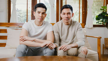 Young Asia gay couple propose at modern home, LGBTQ men happy smiling have romantic time while proposing and marriage surprise wear wedding ring in living room at house. Anniversary romantic concept. Imagens