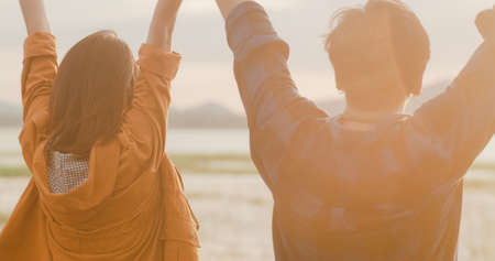 Young asia campers couple run and raised arms at campsite near beach. Happy male and female traveler success and fun when sunset in evening. Outdoor activity, adventure travel, or holiday vacation.