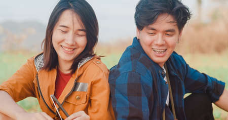 Young asia campers couple camping near seaside. Male and female traveler using smartphone vlog video and live in social media at campsite. Outdoor activity, adventure travel, or holiday vacation.