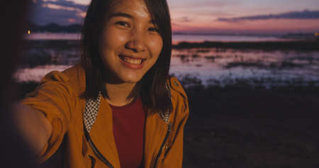 Cheerful traveler Asia lady with backpack recording video vlog live streaming on phone upload in social media in camping on beach at night. Girl happy enjoy holiday trip. Lifestyle travel and relax.