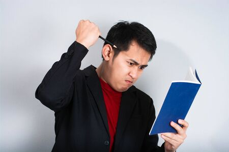 businessman in anger with fists clenched screaming,Angry businessman shout with book Stock Photo