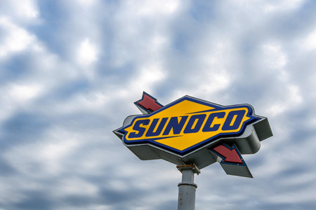 Garden State Parkway, NJ, December 12, 2016: Sunoco sign on a pole at a rest area is seen against cloudy skies. Stock Photo - 73837118