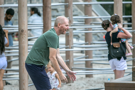 New York, September 11, 2016: Noah Emmerich is enjoying himself playing with kids on a playground in Central Park. Editorial