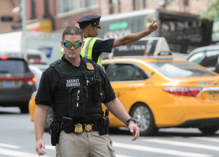 A Secret Service agent is helping direct traffic and keeping the reserved lane on the 2nd Avenue clear during the UN General Assembly. Editorial