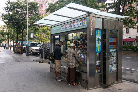 manhattans: New York, September 28, 2016: Two people are making purchases at a newsstand in Manhattans Upper West Side. Editorial