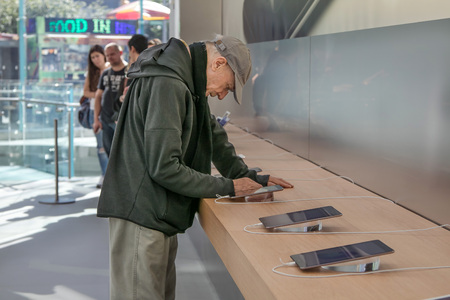 manhattans: New York, October 5, 2016: An elderly man is looking at an iPad tablet in the Apple store on Manhattans Upper West Side.