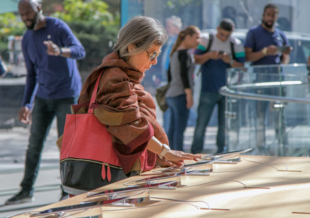 manhattans: New York, October 5, 2016: An elderly woman is looking at an iPad tablet in the Apple store on Manhattans Upper West Side. Editorial