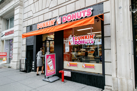 New York, January 21, 2017: A woman is walking into a Dunkin Donuts store on west 72 street in Manhattan. Editorial