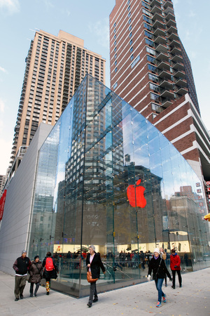 New York, December 3, 2016: People are walking by the Apple Store on Broadway and West 67th street. The logo in the store is illuminated red.