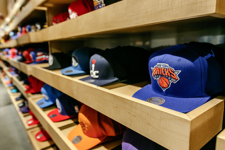fandom: New York, February 21, 2017: A wide vareity of baseball caps with NBA team logos fill the shelves of the NBA store in Manhattan. Editorial