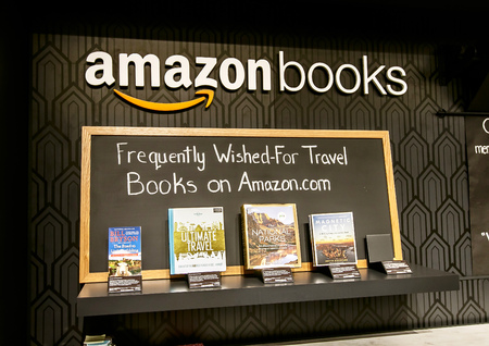 New York, June 1, 2017: A few books are put on display at the wall behind the checkout counter in a newly opened Amazon Books store in Time Warner Center. 免版税图像 - 80068348