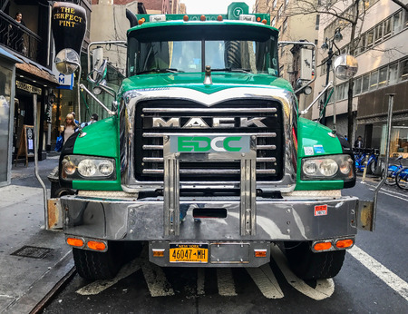 New York, January 12, 2017: A green powerful garbage truck is parked in Manhattan. Garbage is being loaded at the back. Reklamní fotografie - 83708257