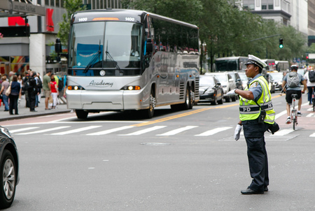New York, July 27, 2017: African American police woman is directing traffic during the day in Manhattan.